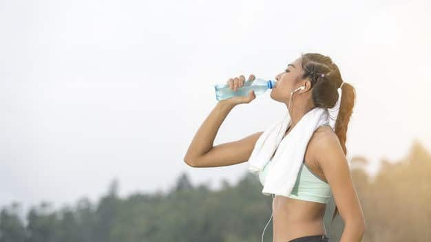 young-asian-woman-thirsty-and-drinking-pure-water-after-jogging