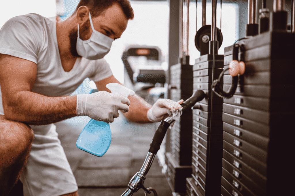 aluno higienizando aparelho na academia na pandemia